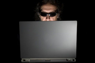 Male with sunglasses looks at the illuminated laptop screen.