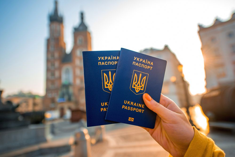 Female hands holding Ukrainian abroad passports on the Krakow city center background