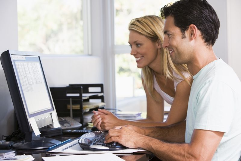 Couple in home office using computer and smiling