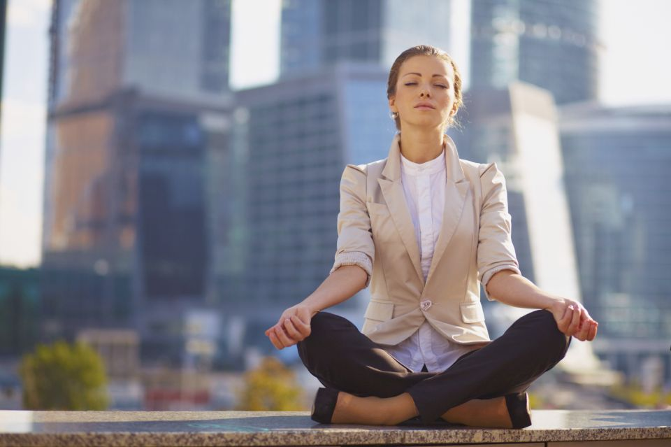Business woman meditating outdoor over building background