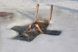 Man dive in ice-holes in cold water in holiday the Christening .